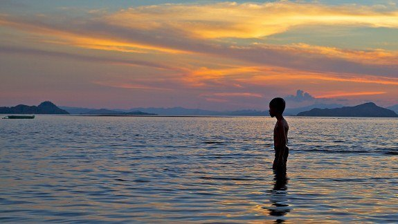 Indonesia boy in water sunset