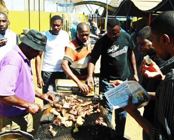 men eating kapana in Namibia