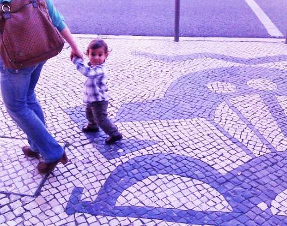 boy walking on lisbon mosaic tile sidewalk