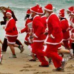 New Zealand santas running on beach