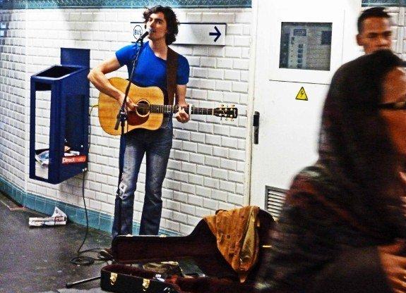 Street musicians of Paris guitar player metro open case