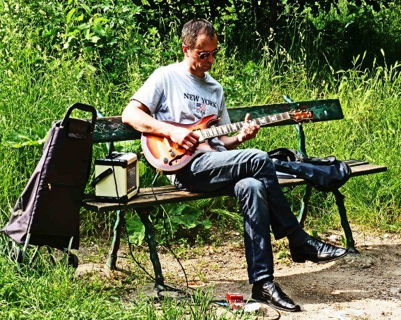 Street musicians of Paris guitar player park bench