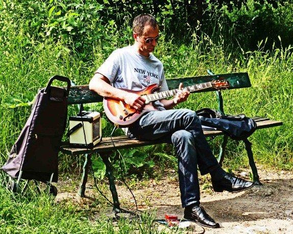 Street musicians of Paris guitar player park bench