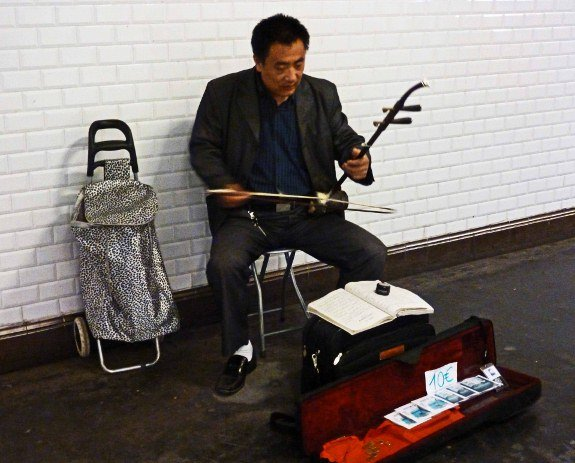 Street musicians of Paris metro Asian instrument case open