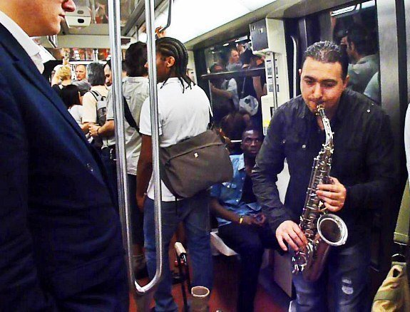 Street musicians of Paris metro sax player man in suit