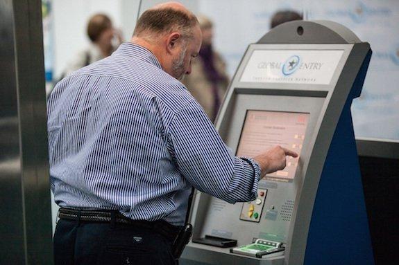 Man using a new Global Entry kiosk at Newark Liberty International Airport.