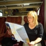 Larissa on a European train reading a Eurail pass map