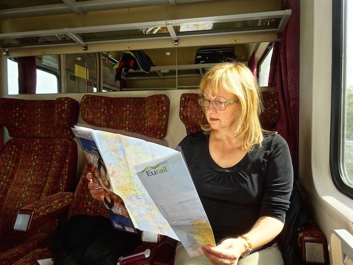 Sitting on European train with Eurail pass and Eurail map