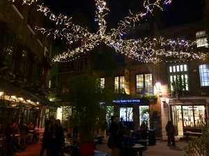 Star shaped design of christmas lights above a small shopping square in London