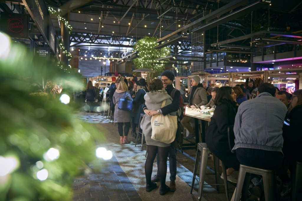 Couple embracing by Christmas decorations at Old Spitalfields market