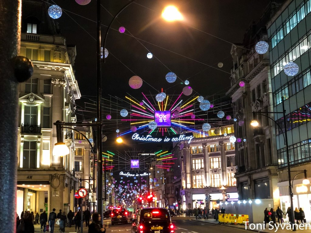 Oxford street at night, Christmas lights above, London taxi below