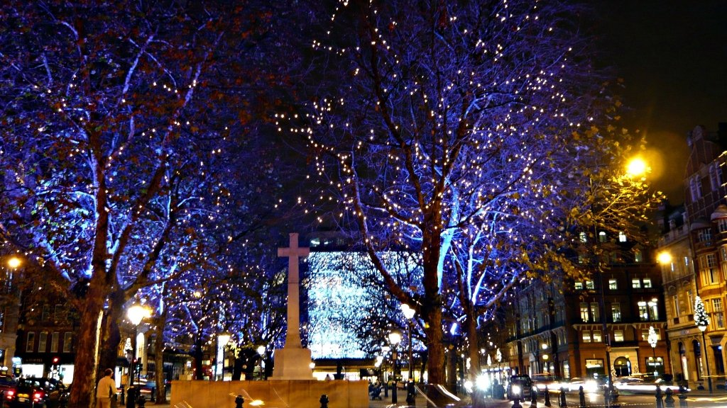 Square with bare trees lit by tiny white lights