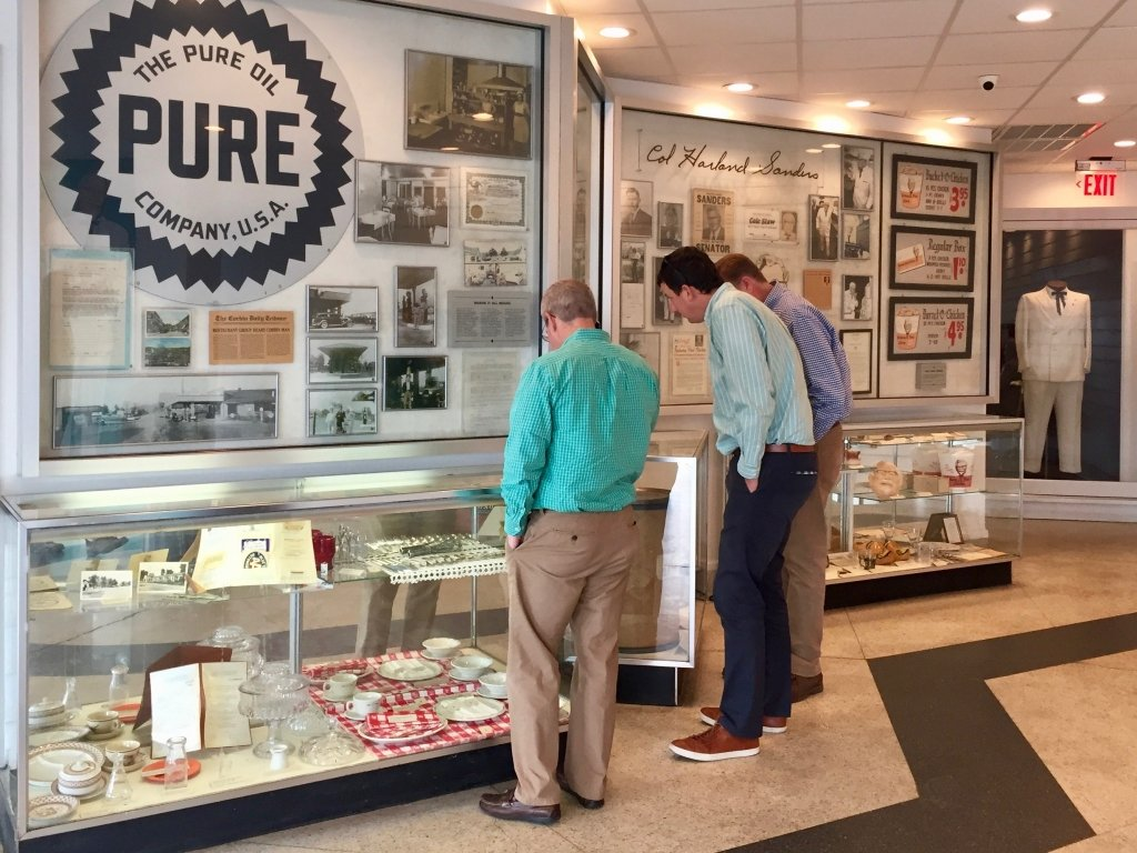 Display cases at the museum portion of Sanders Cafe. (White Suit in background)
